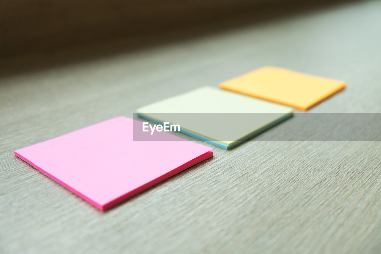 Close-Up Of Colorful Adhesive Notes On Wooden Table