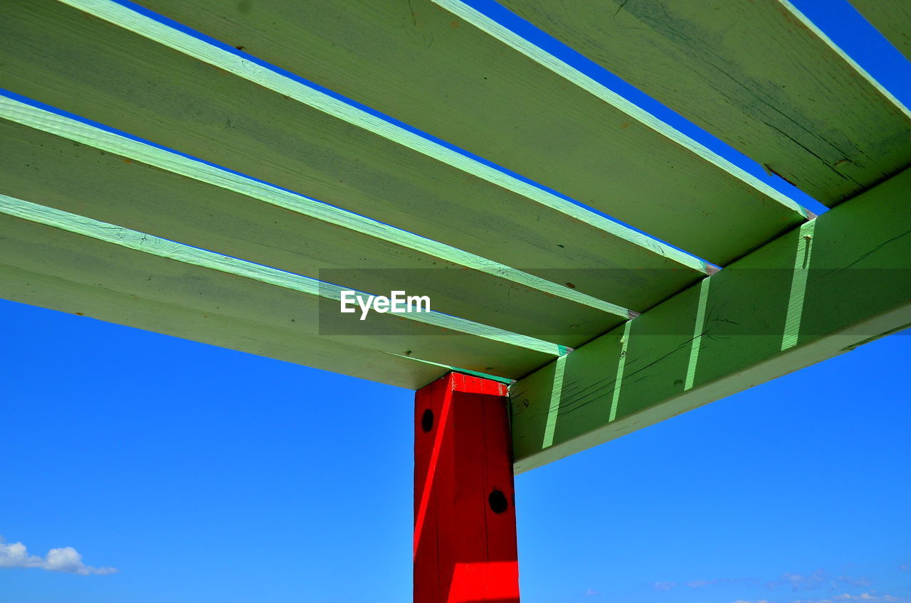 blue, red, low angle view, day, architecture, sky, built structure, no people, nature, sunlight, outdoors, pattern, green color, close-up, clear sky, wood - material, roof, metal, multi colored, architectural column, girder