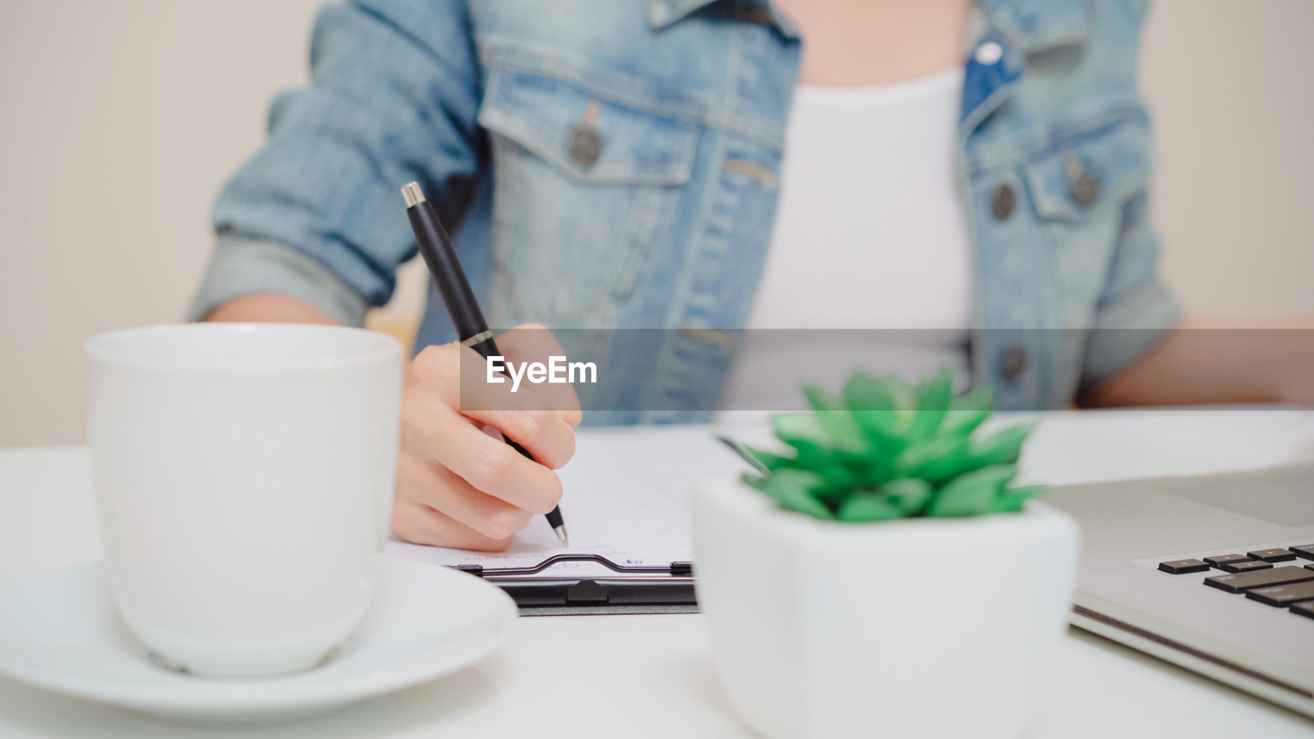 Midsection of young woman writing on paper in office