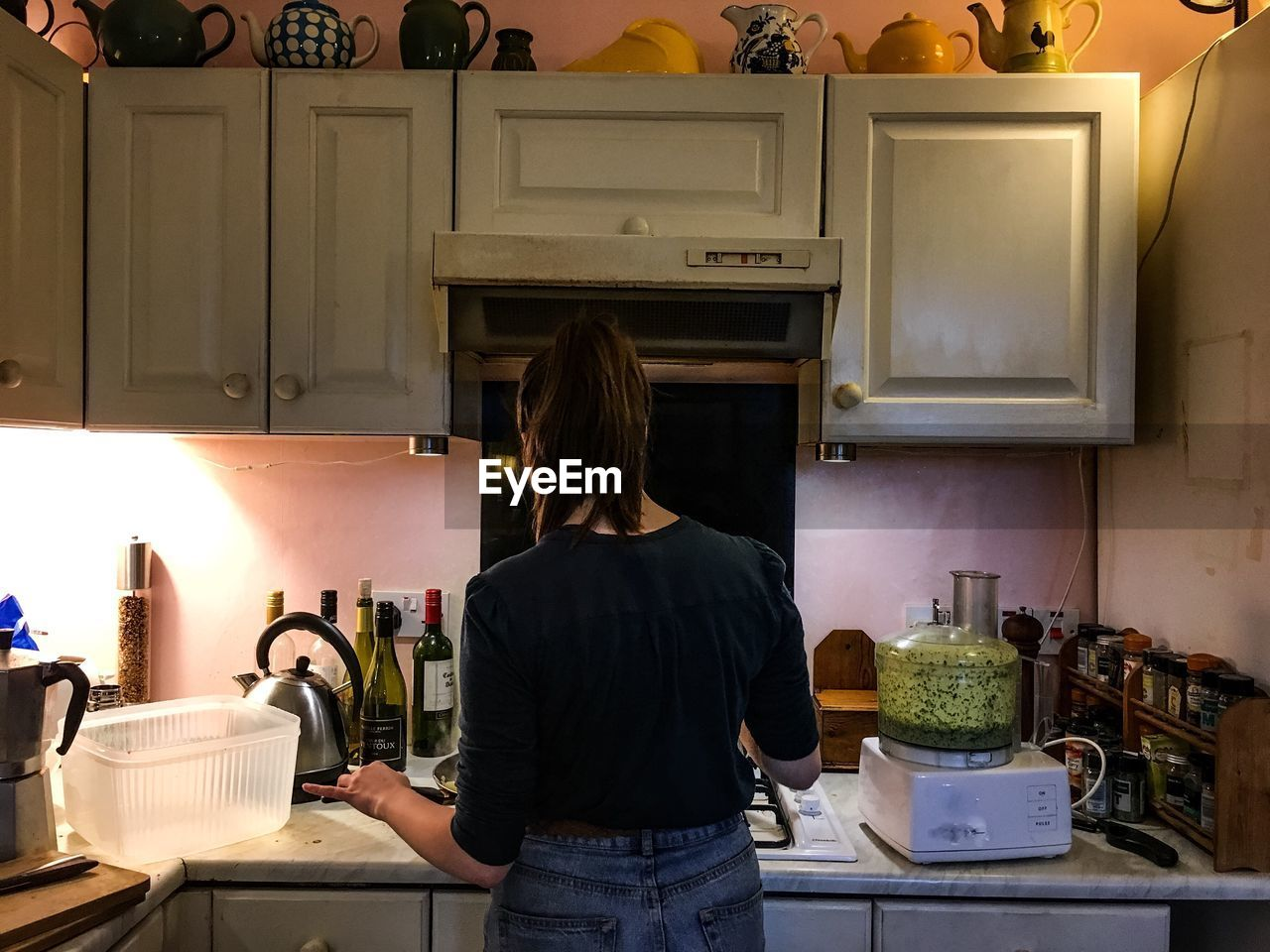 Rear View Of Woman Cooking In Kitchen At Home