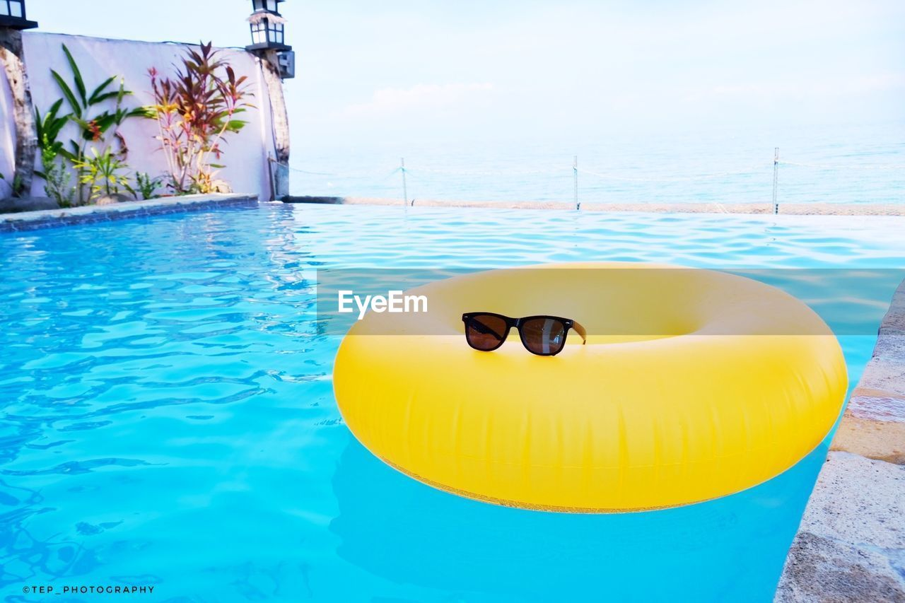 pool, swimming pool, water, yellow, inflatable, nature, tube, floating, tubing, day, blue, floating on water, no people, outdoors, sunlight, poolside, waterfront, sky, close-up, pool raft, turquoise colored