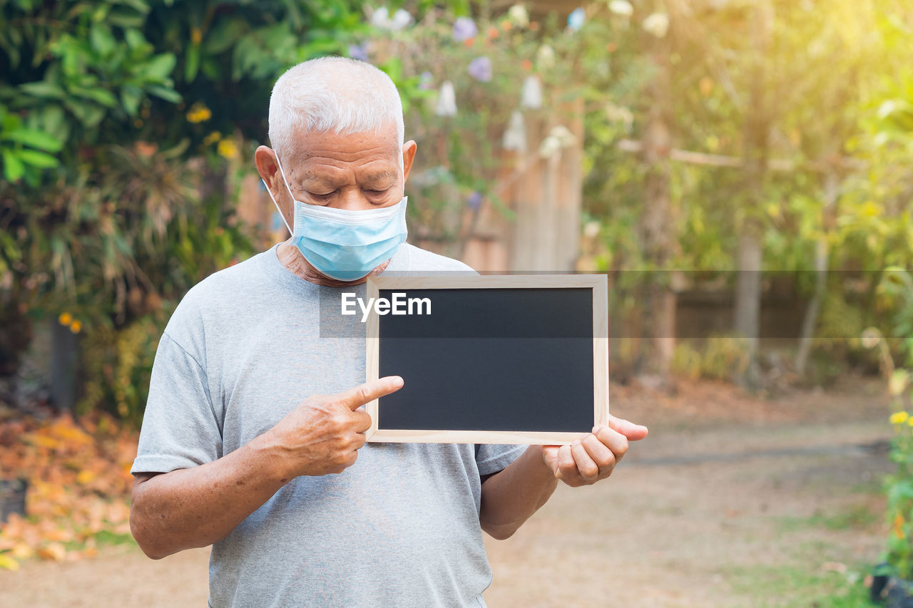 A portrait of an elderly man wearing a face mask and holding a blackboard standing in a garden