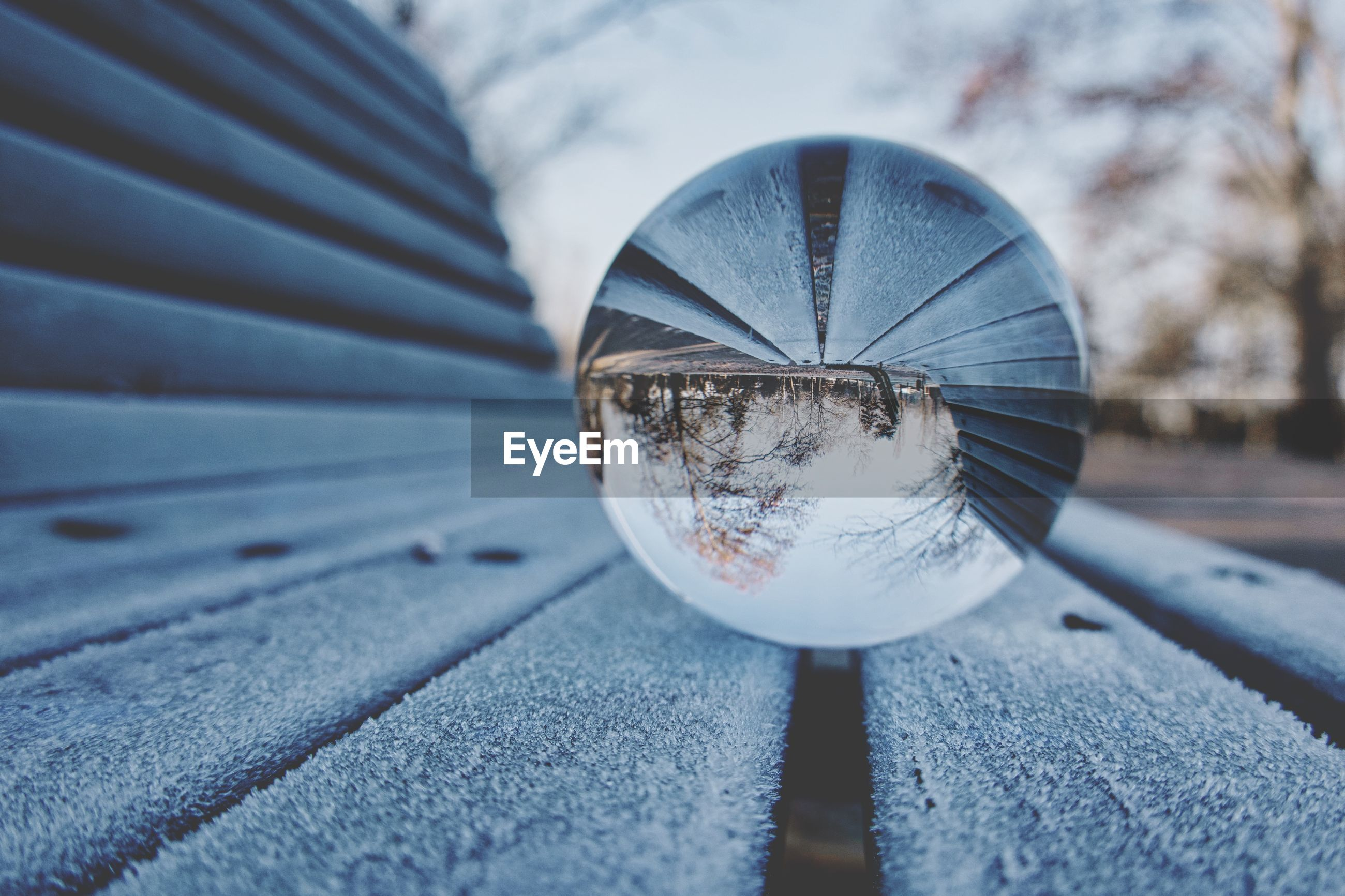 Close-up of crystal ball on frozen wooden bench