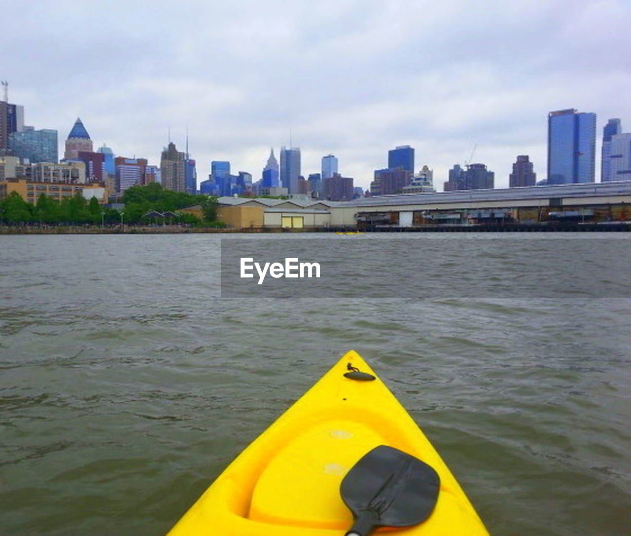 yellow, city, architecture, sky, built structure, building exterior, skyscraper, cloud - sky, water, river, outdoors, urban skyline, day, cityscape, nautical vessel, no people, kayak, close-up