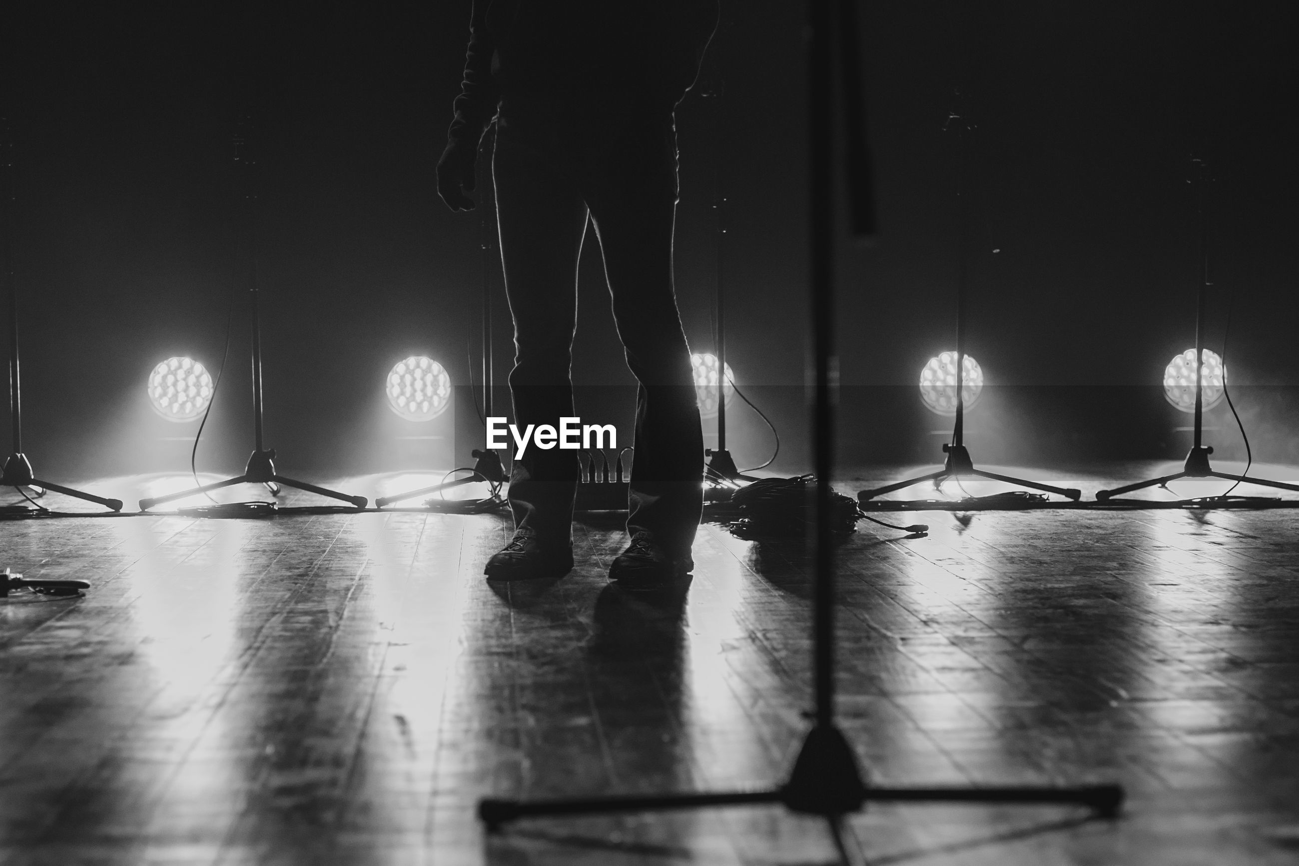 Low section of man standing on illuminated stage