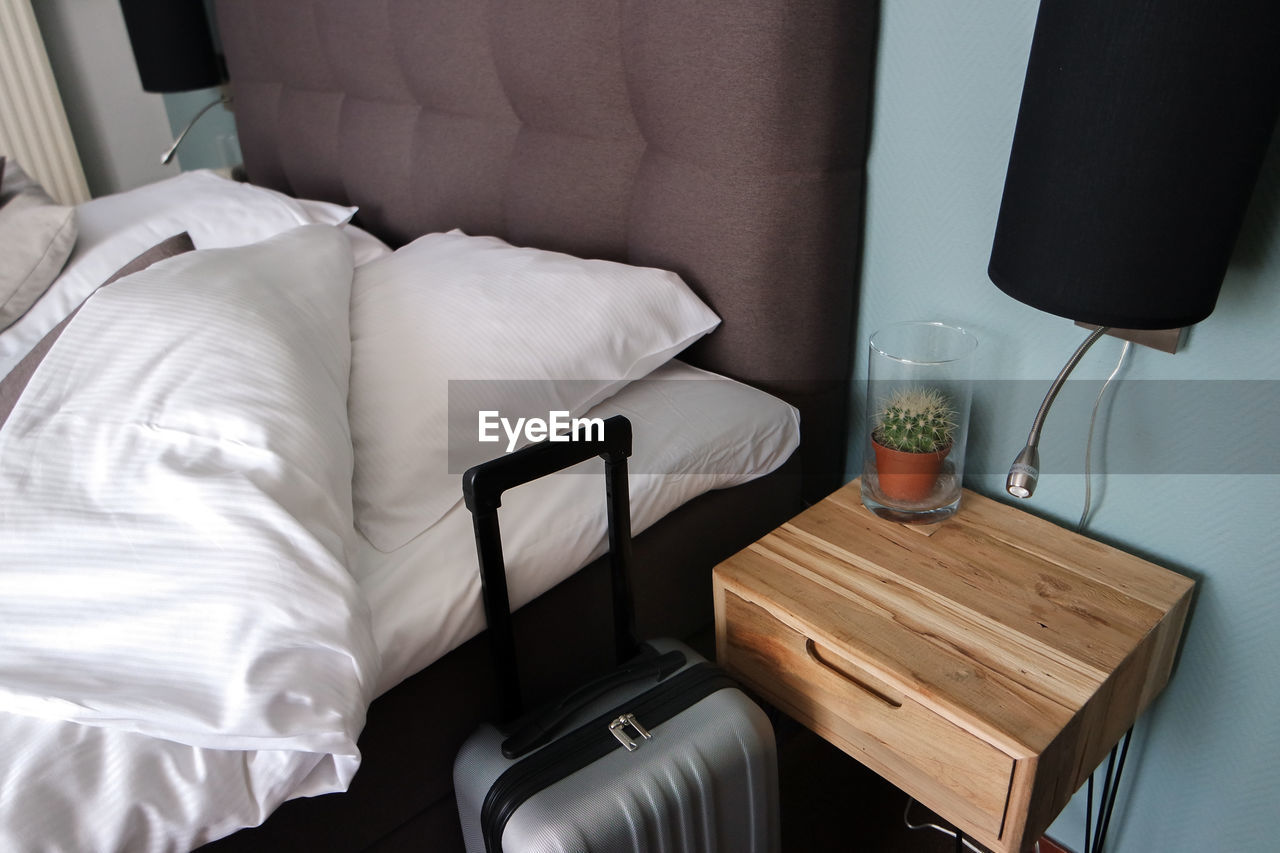 High angle view of suitcase by bed in bedroom
