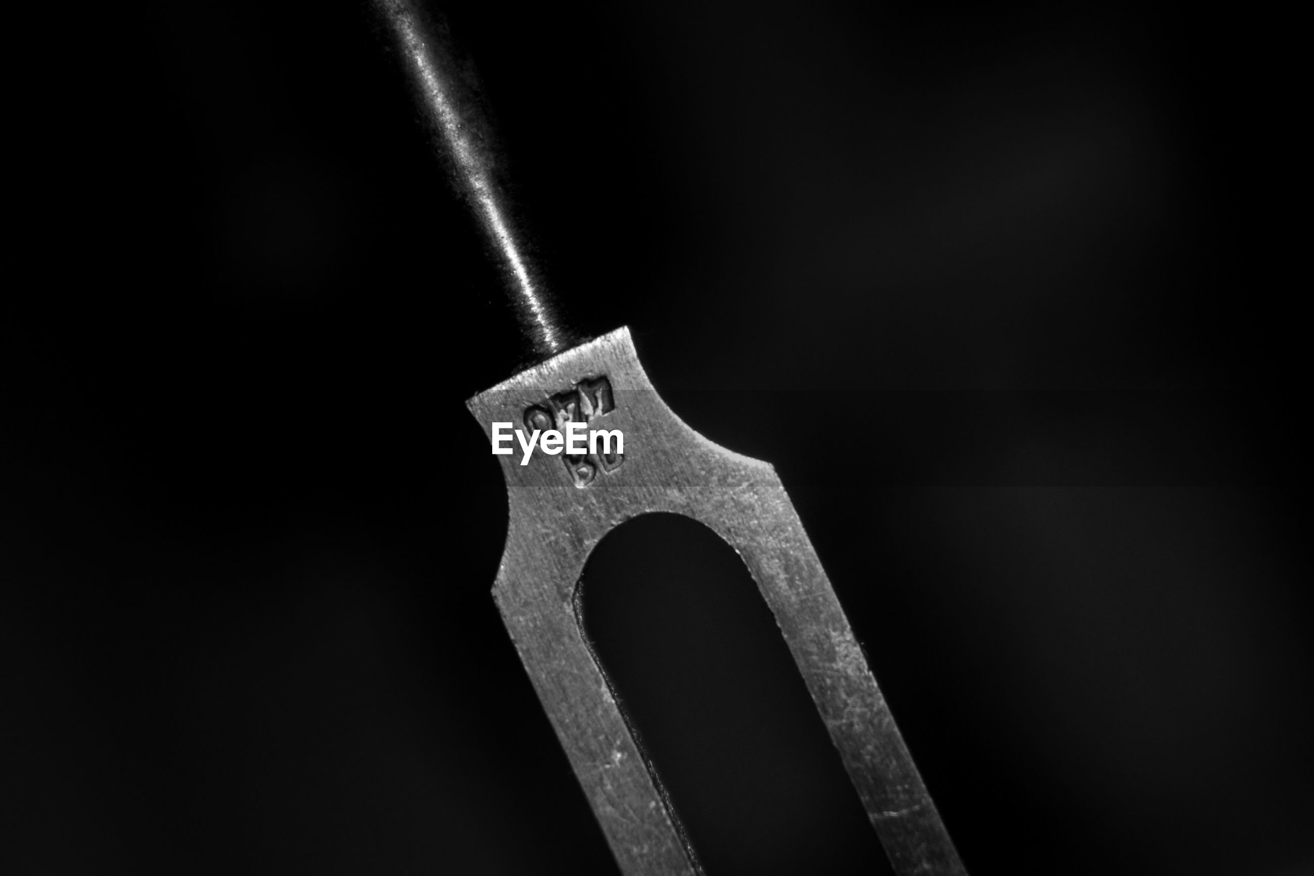 Close-up of tuning fork against black background