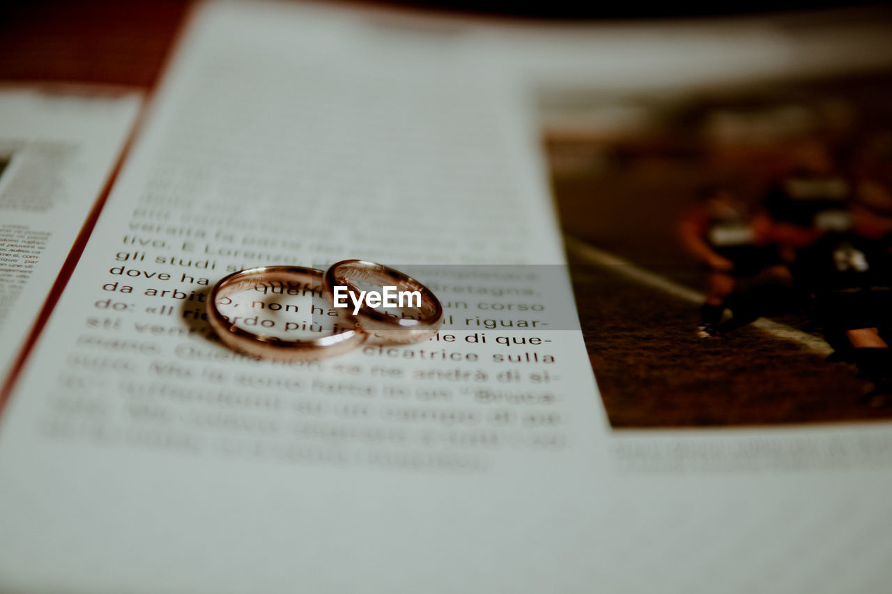 selective focus, ring, jewelry, indoors, text, no people, wedding, close-up, publication, still life, table, wedding ring, book, western script, communication, event, positive emotion, love, paper, life events, personal accessory