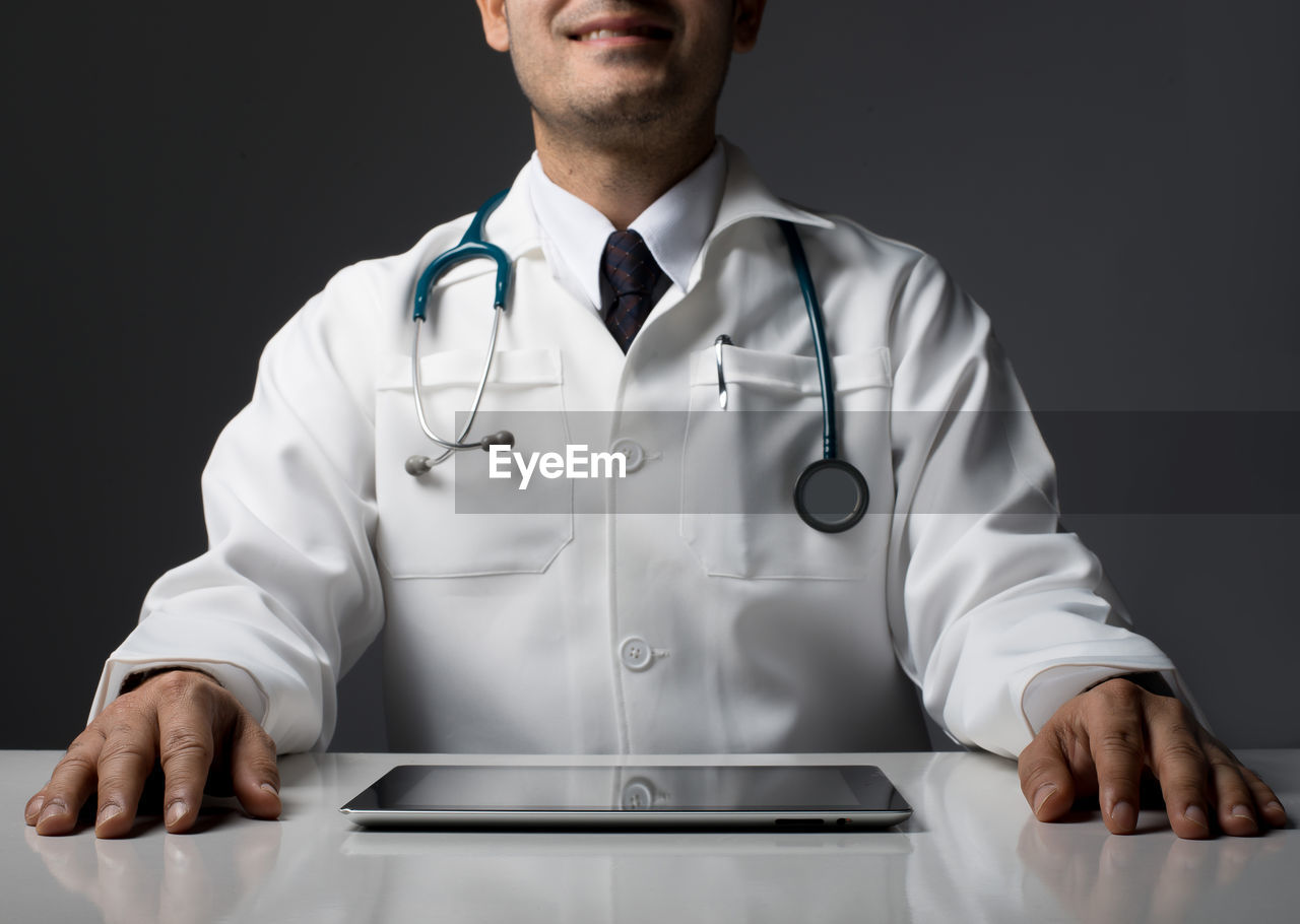 Midsection Of Doctor With Digital Tablet On Table Over Black Background