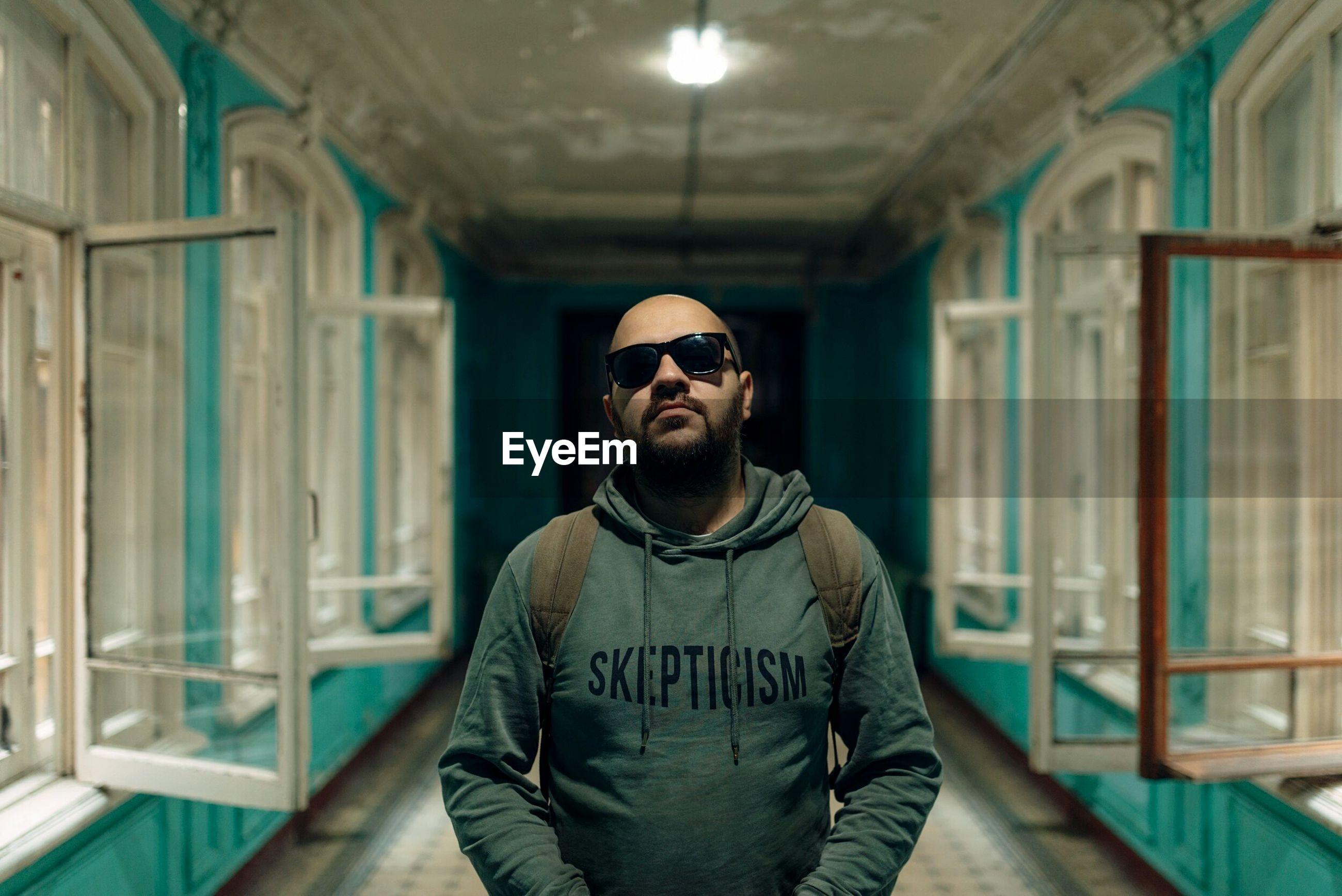 Portrait of man wearing sunglasses standing amidst open windows in corridor