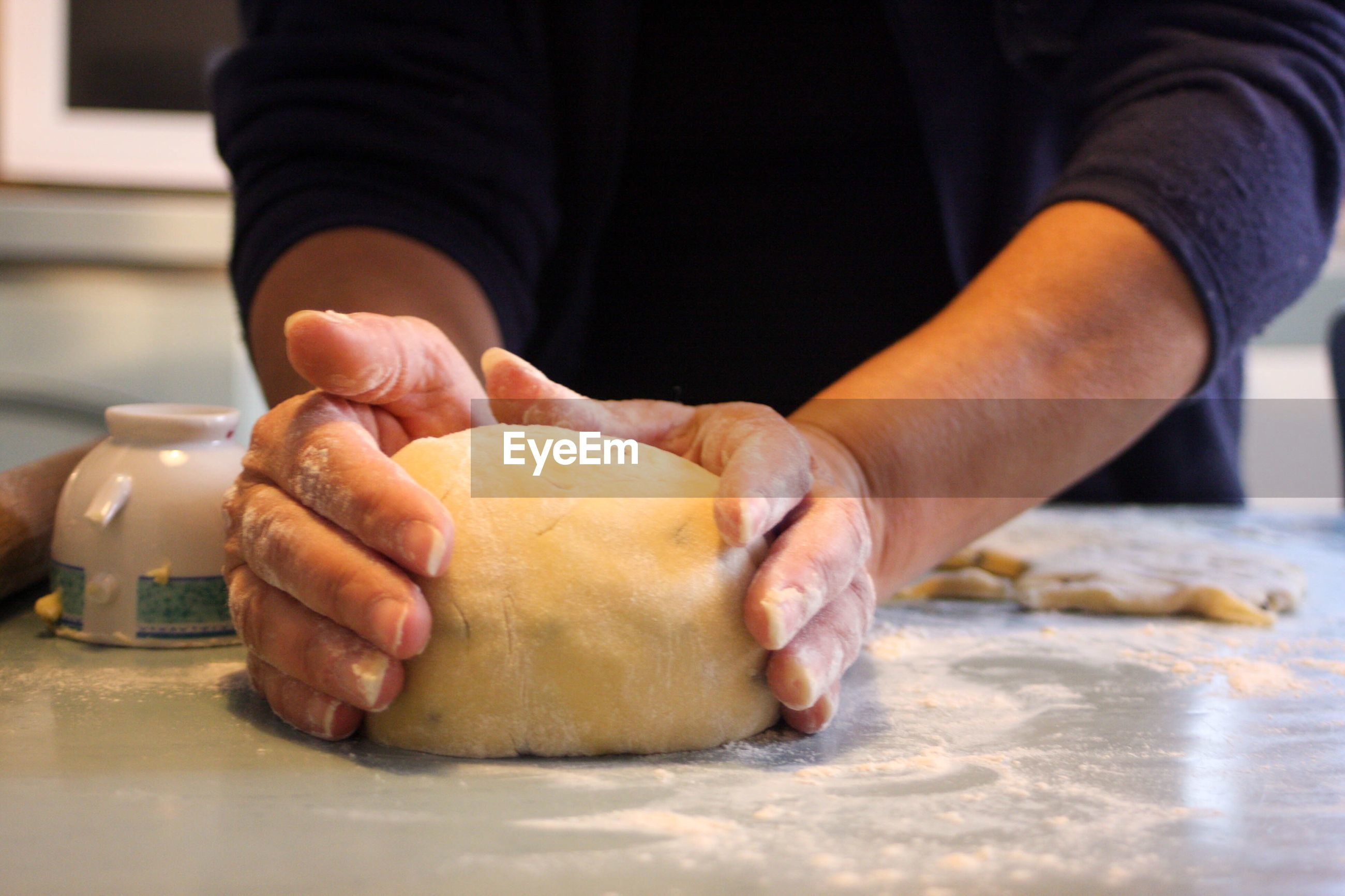 Midsection of woman kneading dough on table