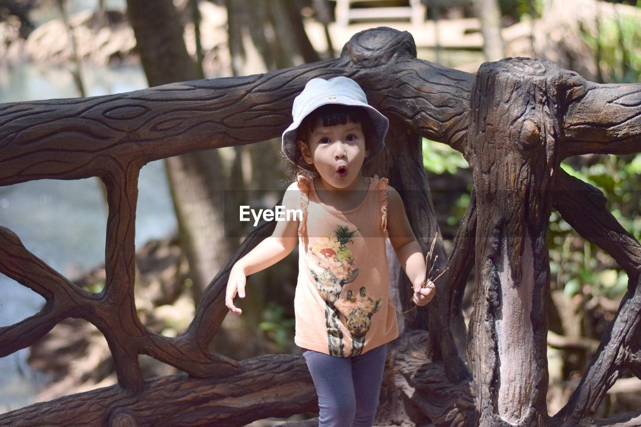 Portrait Of Surprise Girl Standing Against Wooden Railing