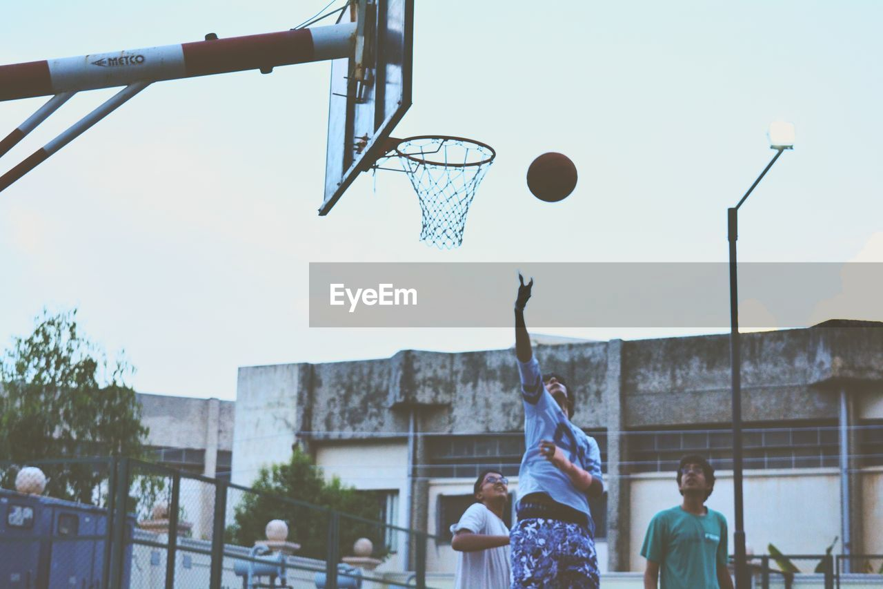 Teenagers playing basketball against sky