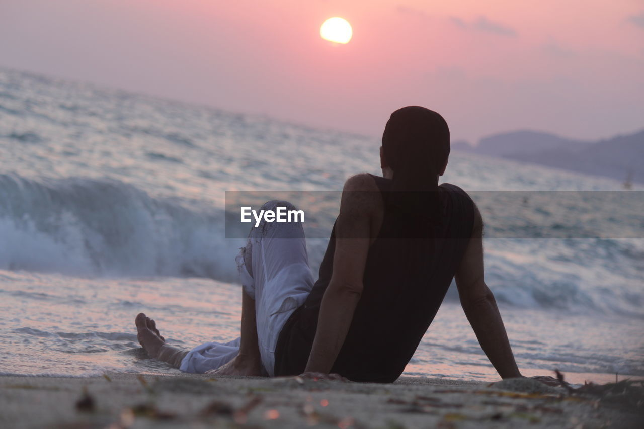 Man Sitting At Beach Against Sky During Sunset
