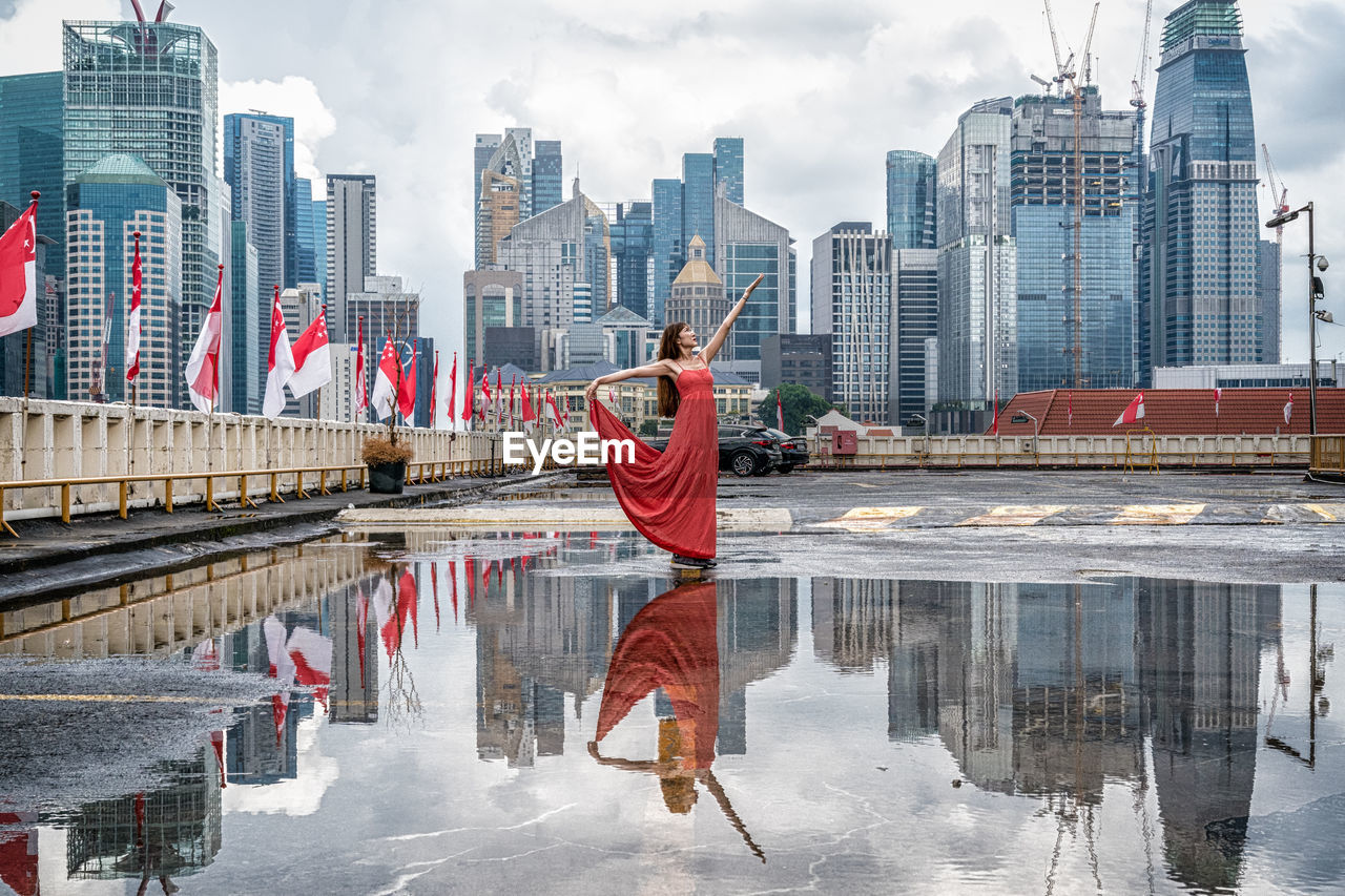 Reflection Of Woman And Buildings On Puddle In City