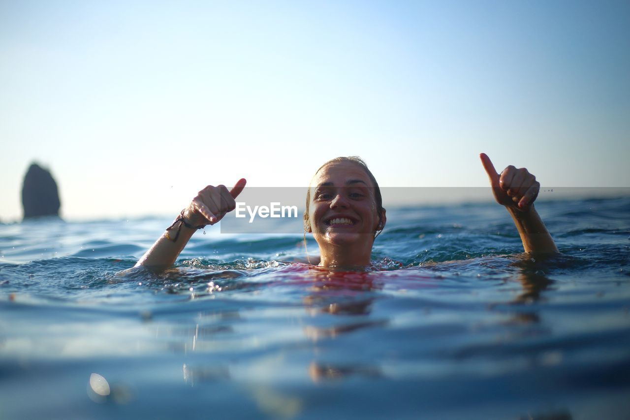 Portrait of smiling young woman swimming in sea
