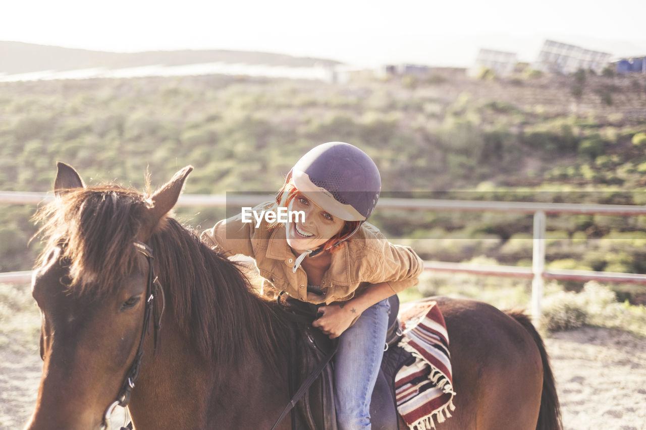 Portrait Of Smiling Woman Riding Horse On Landscape