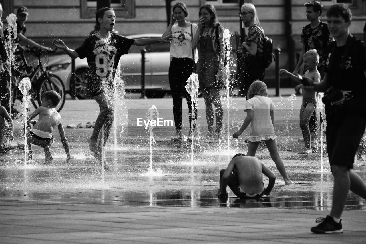 motion, group of people, water, real people, leisure activity, splashing, lifestyles, day, enjoyment, nature, women, people, men, blurred motion, swimming pool, fun, arts culture and entertainment, pool, child, outdoors, spraying