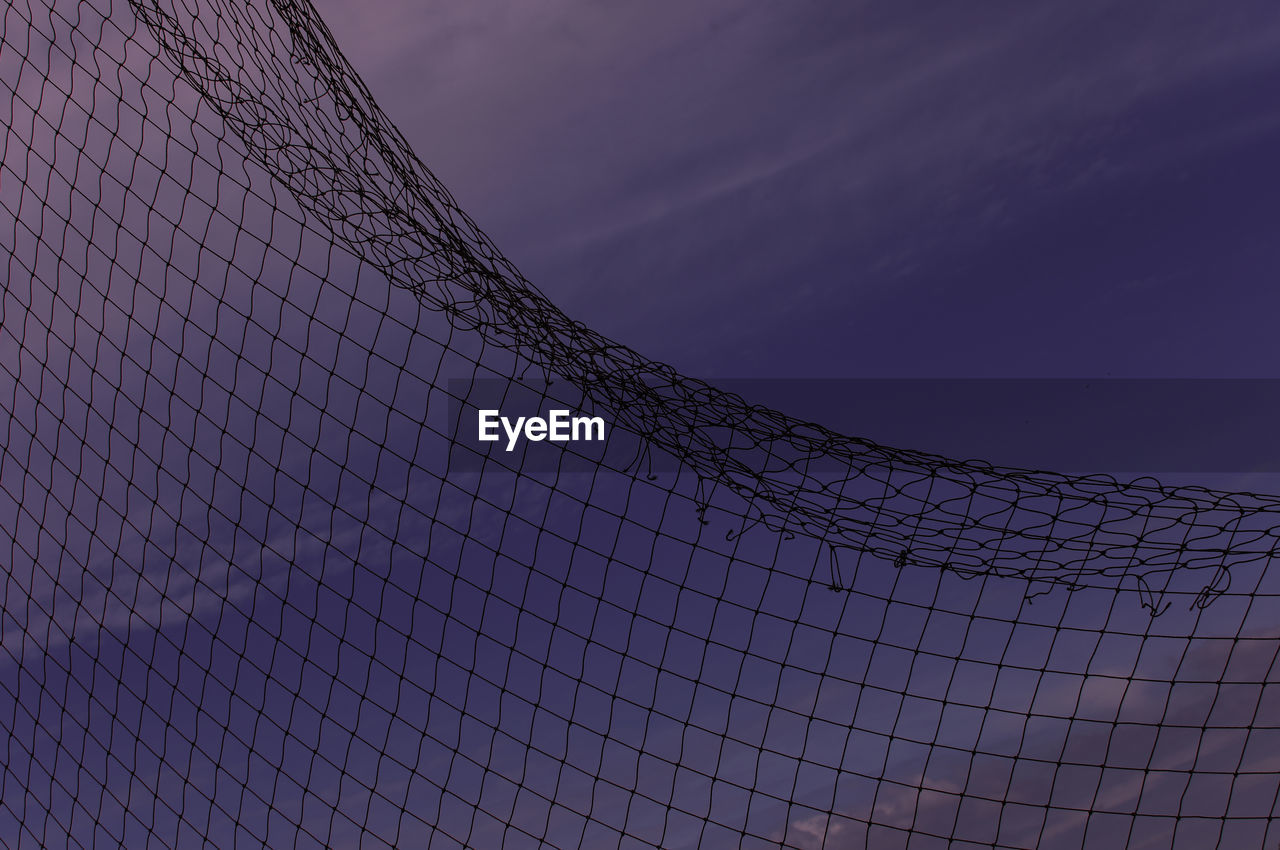 low angle view, sky, no people, sport, pattern, fence, nature, security, protection, barrier, net - sports equipment, boundary, outdoors, architecture, day, built structure, dusk, sunset, safety, modern