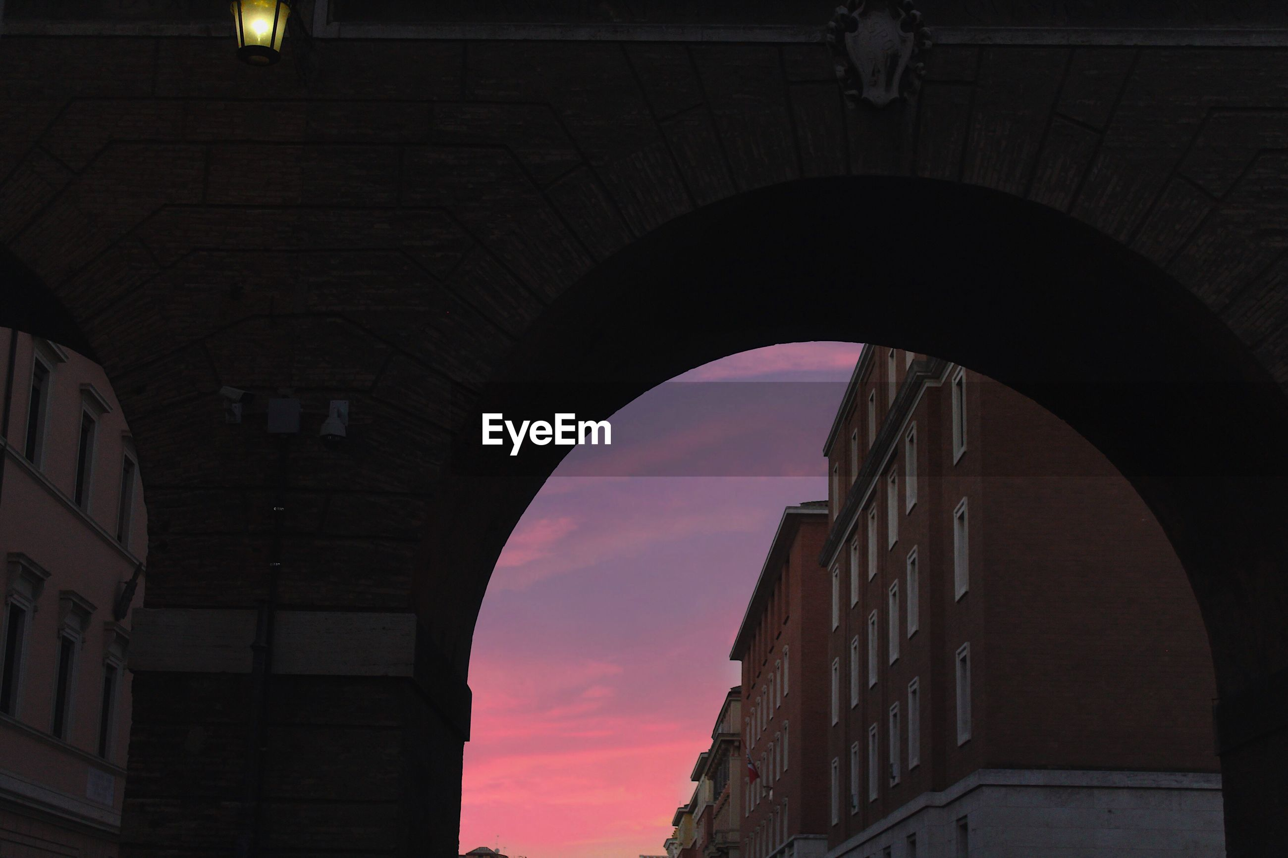 Low angle view of arch bridge against sky at sunset