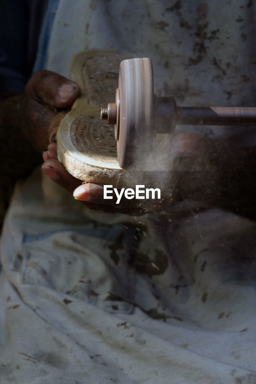 Midsection Of Worker Working In Factory