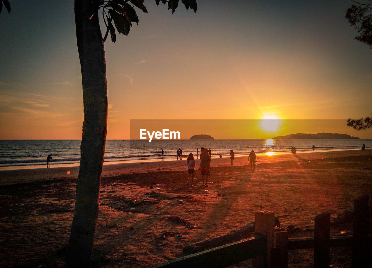 water, sky, sea, sunset, beach, land, scenics - nature, beauty in nature, tranquil scene, sun, tranquility, horizon over water, horizon, nature, silhouette, orange color, idyllic, non-urban scene, sunlight, outdoors, wooden post