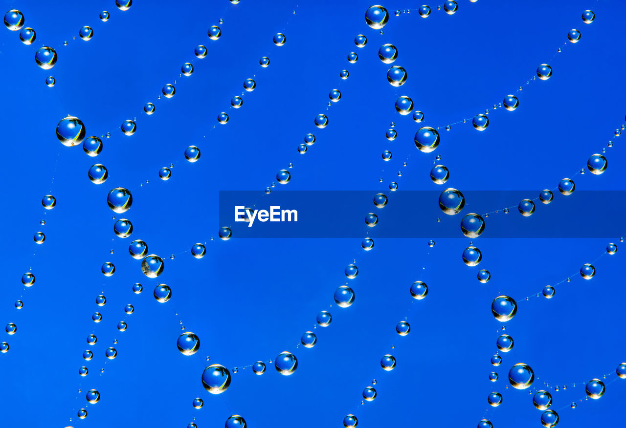 LOW ANGLE VIEW OF WATER DROPS AGAINST BLUE SKY