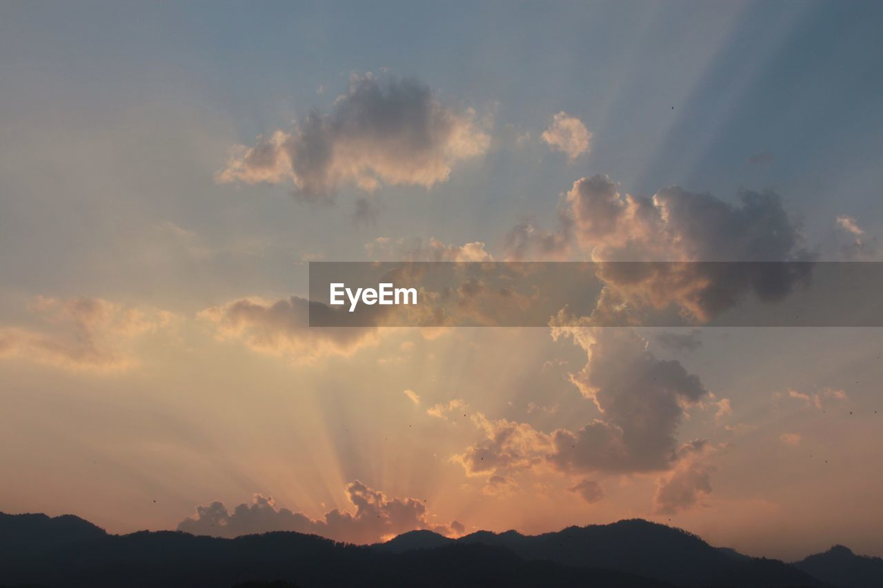 Silhouetted Mountains Against Cloudy Sky At Dawn