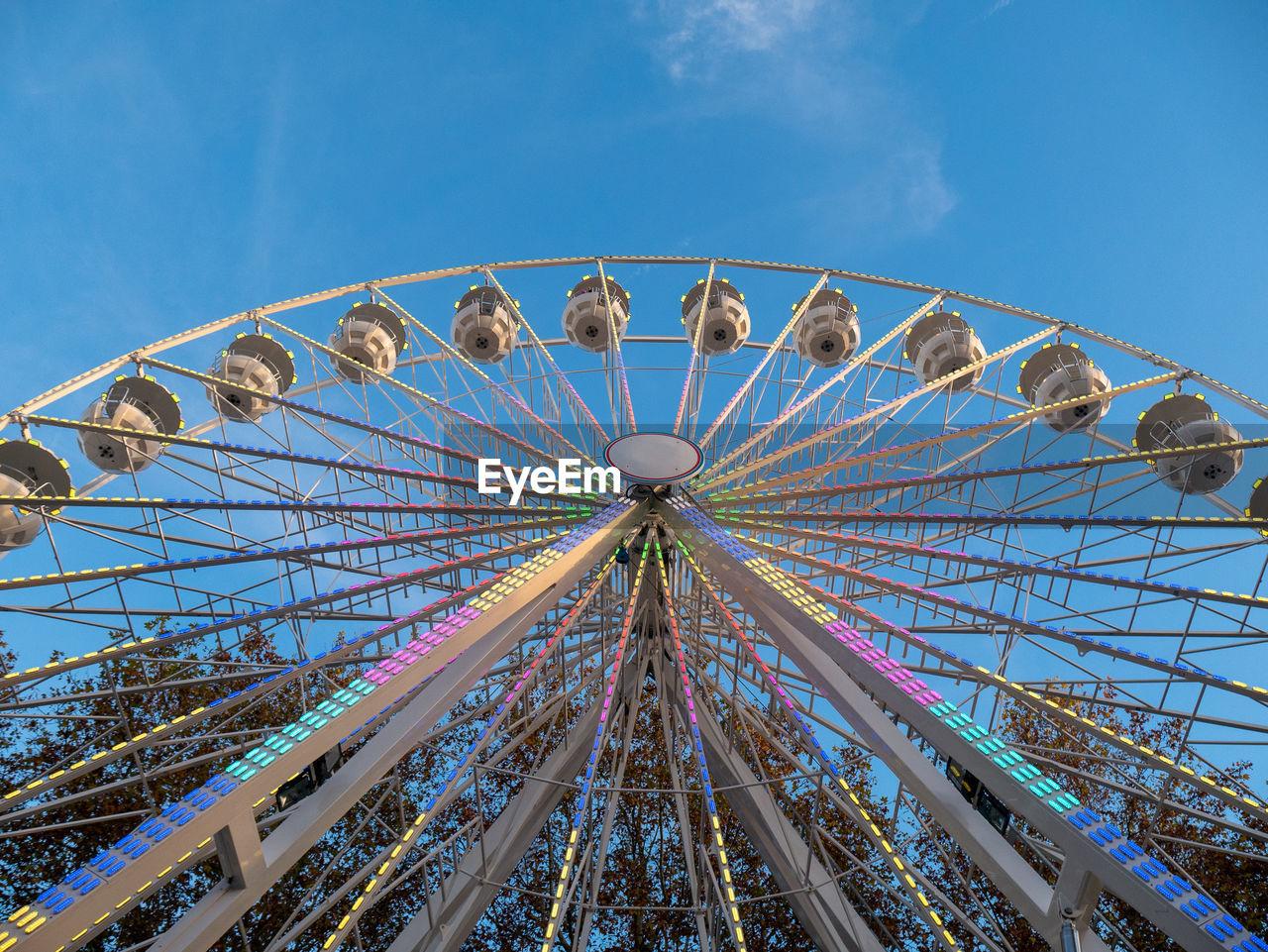 amusement park, amusement park ride, low angle view, sky, ferris wheel, arts culture and entertainment, leisure activity, blue, nature, fairground, built structure, day, metal, architecture, no people, enjoyment, outdoors, clear sky, circle, shape