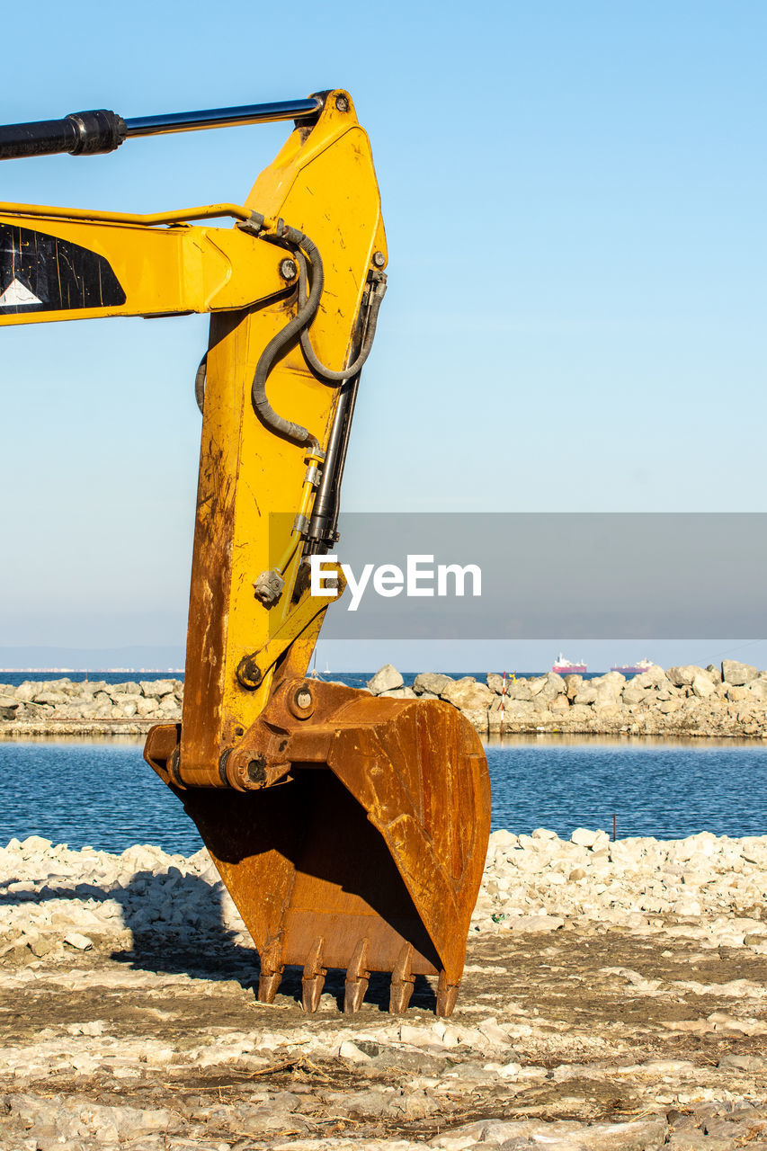 sky, yellow, day, nature, sunlight, land, sea, earth mover, metal, clear sky, no people, construction machinery, water, machinery, outdoors, mode of transportation, beach, bulldozer, construction vehicle