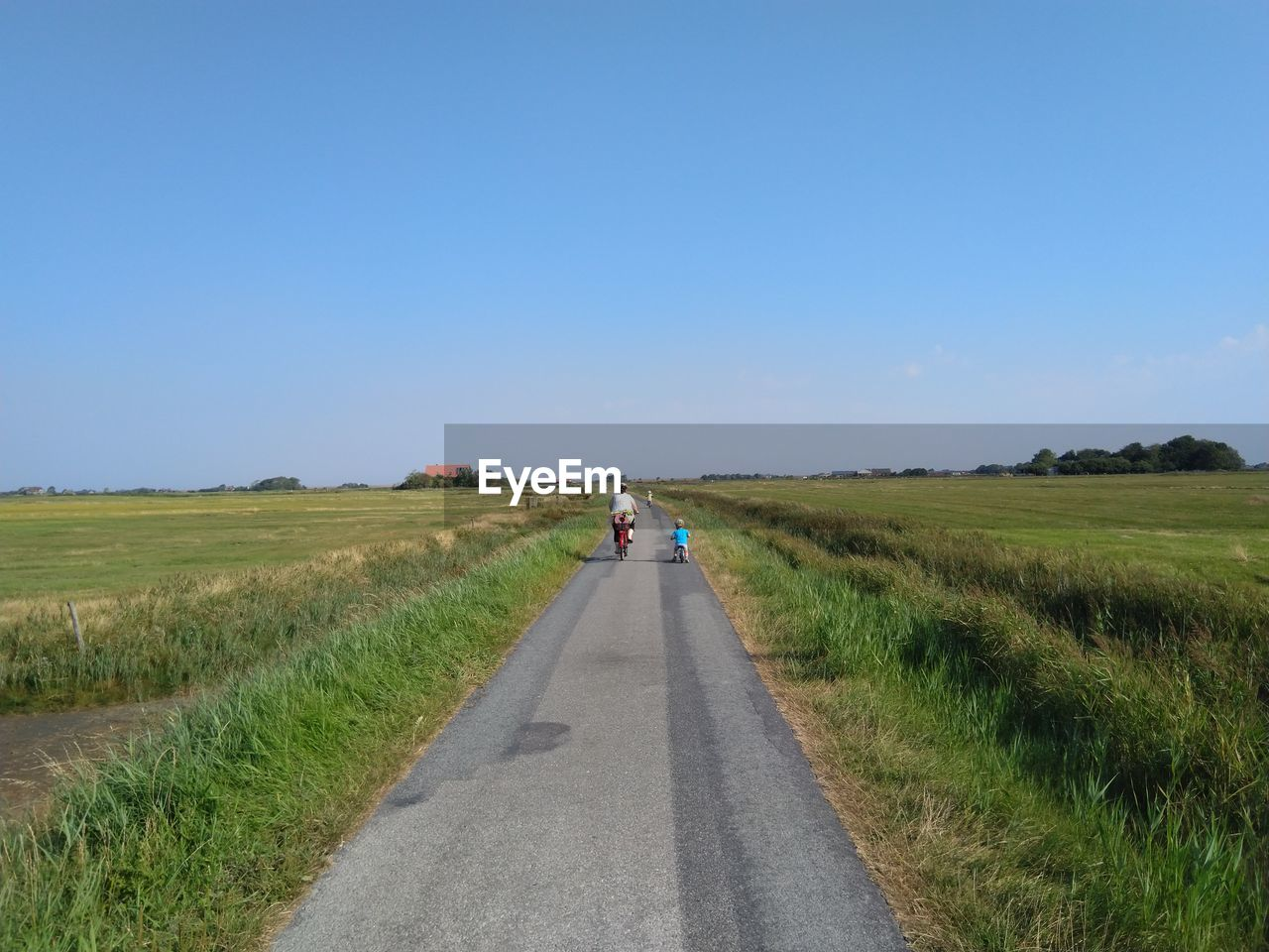 REAR VIEW OF ROAD AMIDST FIELD AGAINST CLEAR SKY