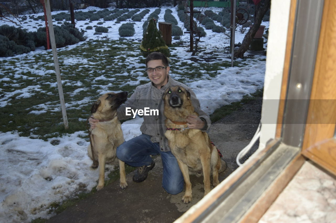 Portrait of young man with dogs outside house during winter