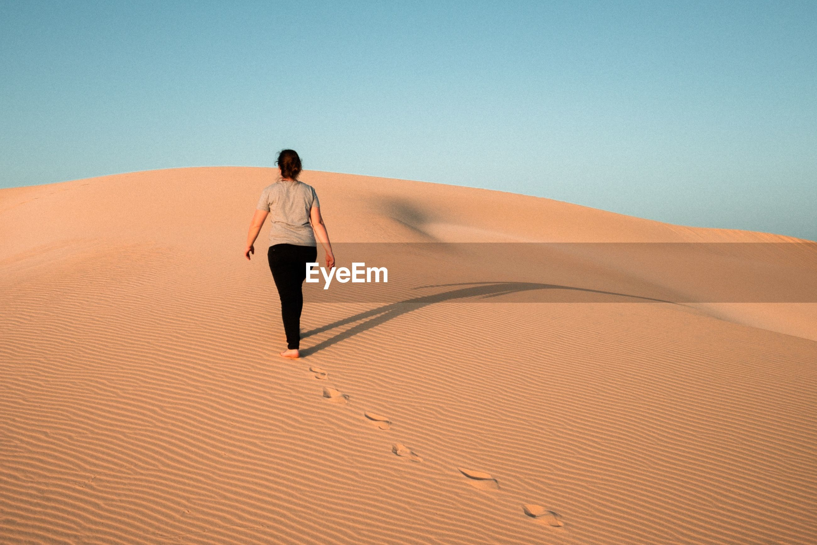 Rear view of woman walking on sand dune at desert against clear sky