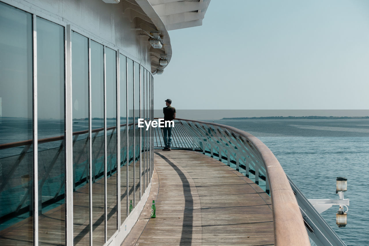 Rear view of man standing on cruise ship sailing in sea