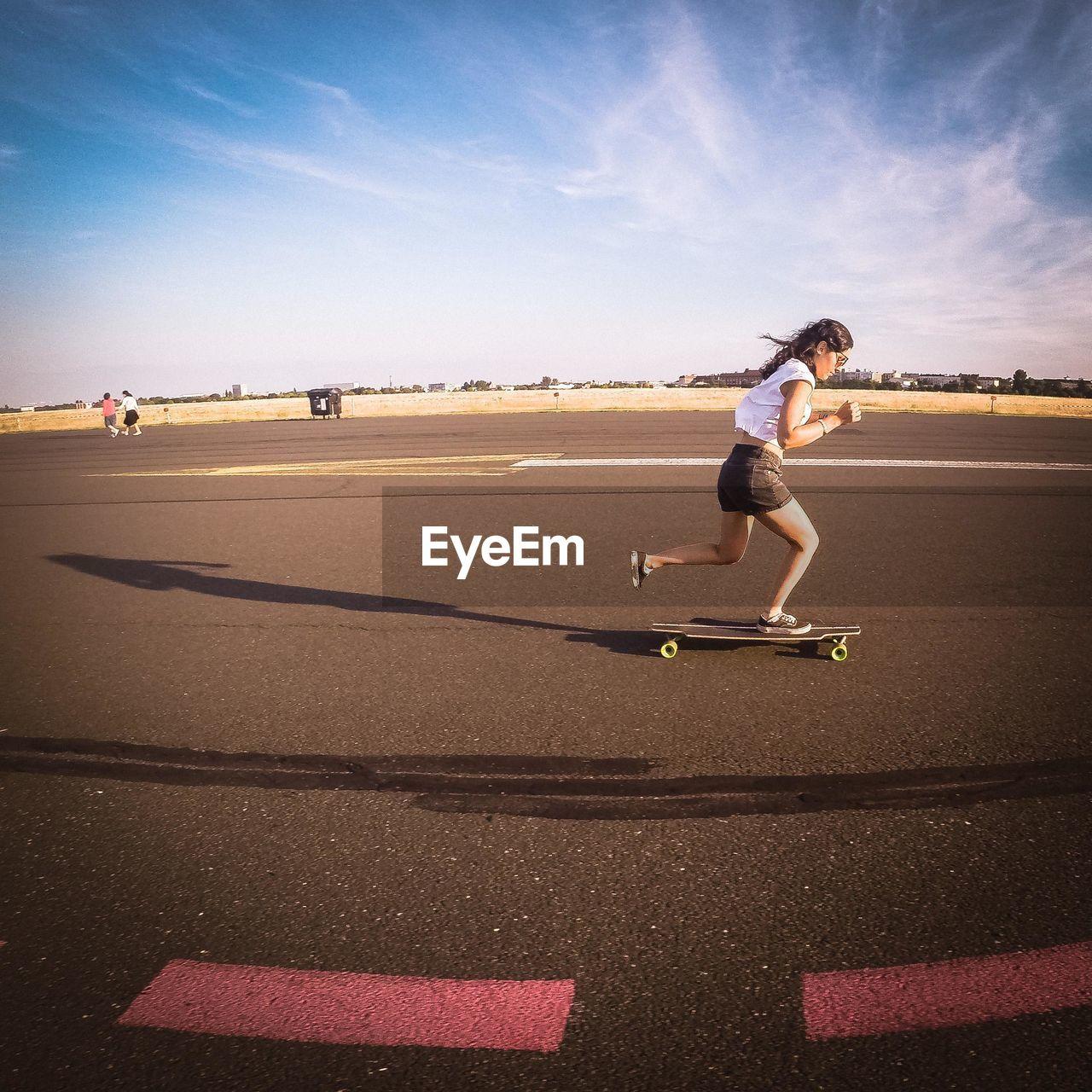 Woman Skateboarding On Road In City