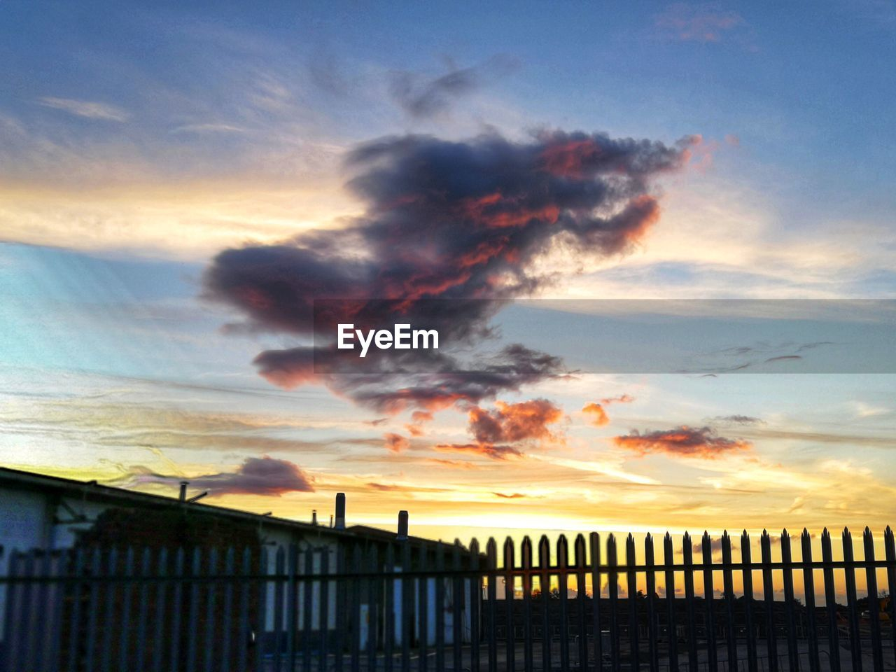 cloud - sky, sky, sunset, building exterior, nature, orange color, no people, architecture, built structure, fence, barrier, silhouette, boundary, beauty in nature, outdoors, scenics - nature, security, safety, protection, railing, ominous