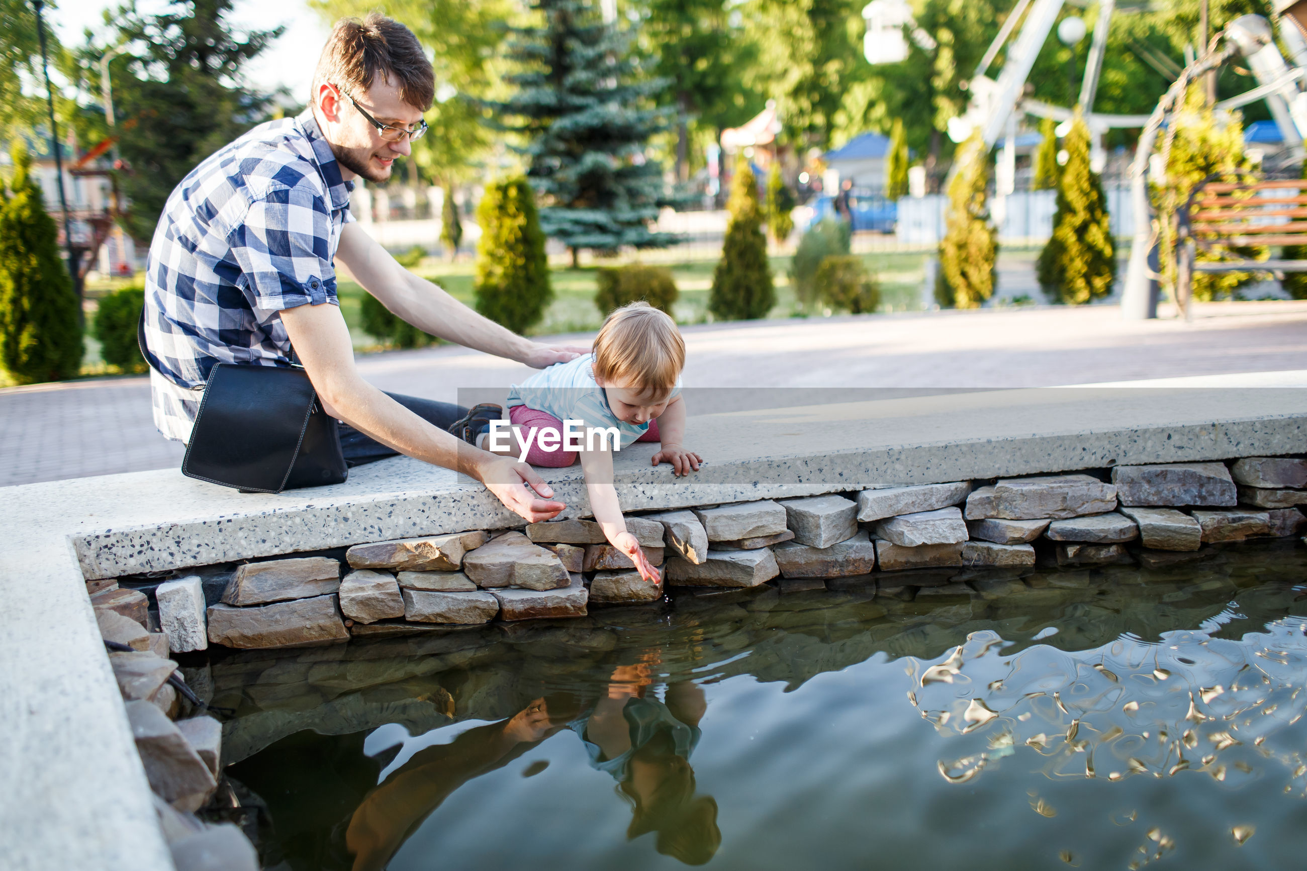 Man looking at daughter playing with water in fountain at park