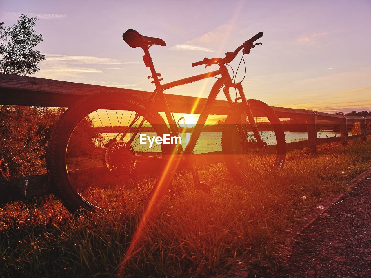 sunset, sky, transportation, bicycle, orange color, nature, land, mode of transportation, land vehicle, field, sunlight, grass, plant, stationary, beauty in nature, lens flare, sun, outdoors, scenics - nature, no people, wheel