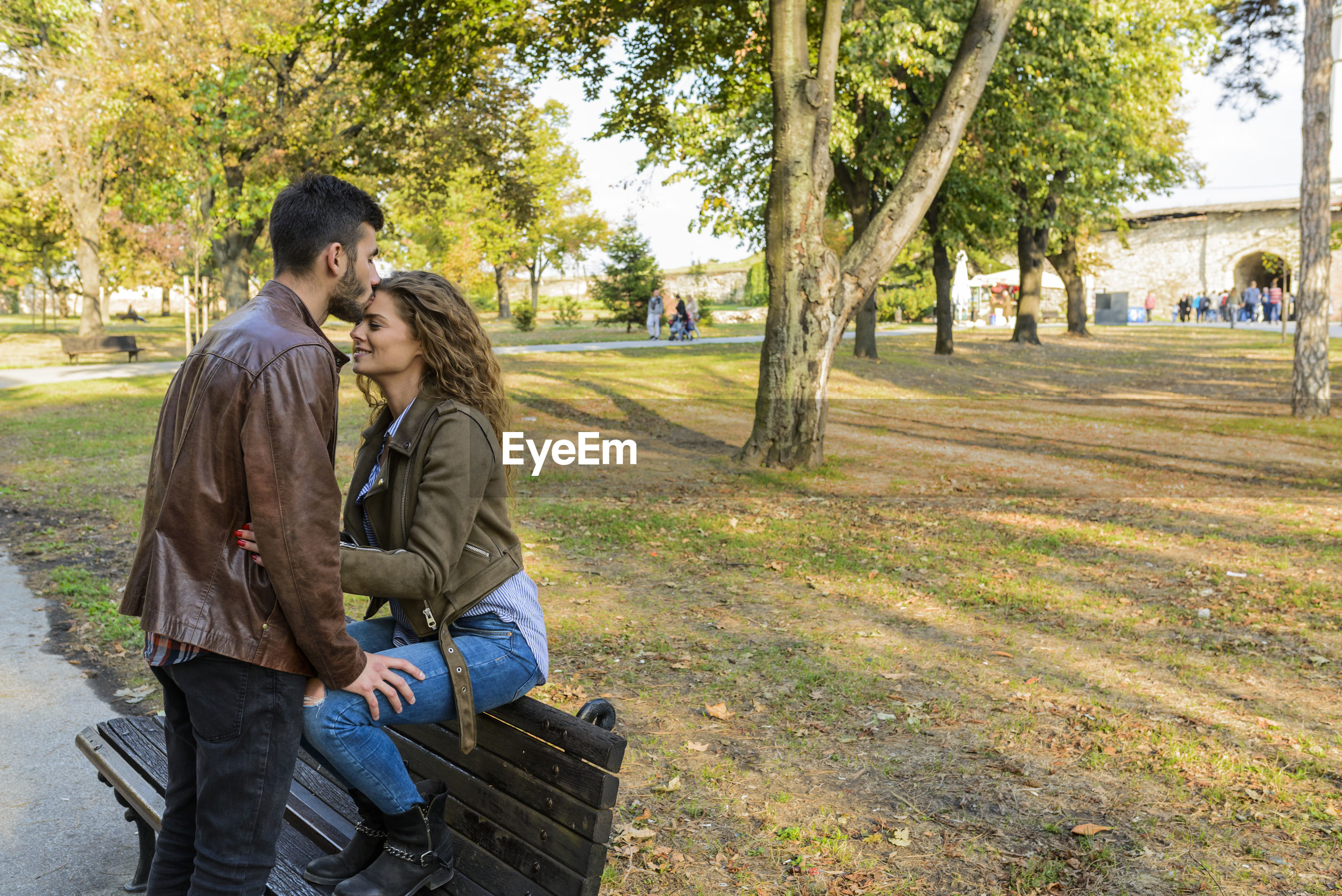 Man kissing on woman heard against trees