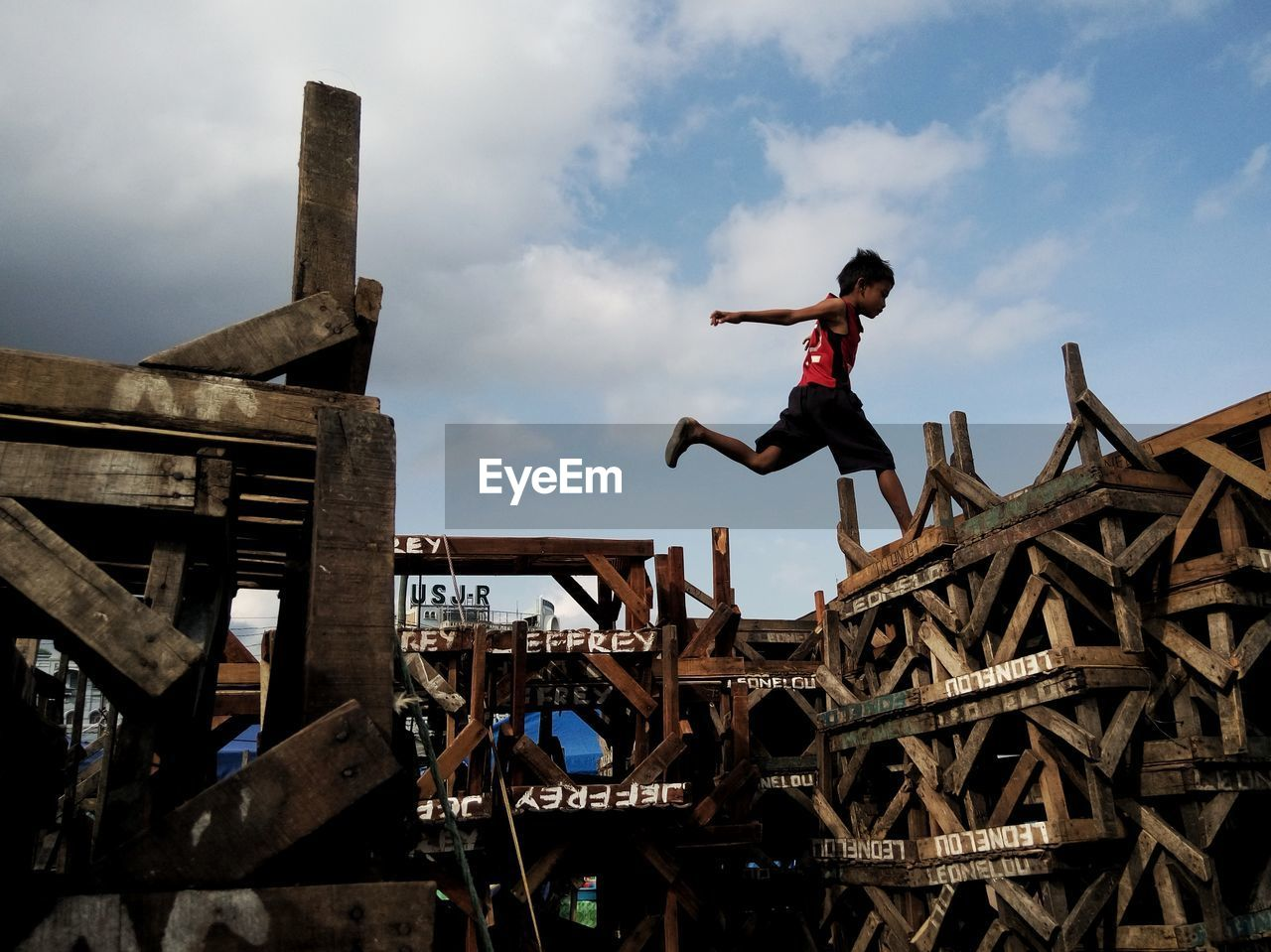 real people, one person, sky, lifestyles, cloud - sky, leisure activity, low angle view, built structure, full length, outdoors, architecture, wood - material, day, playing, boys, childhood, adventure, skill, sport, men, people