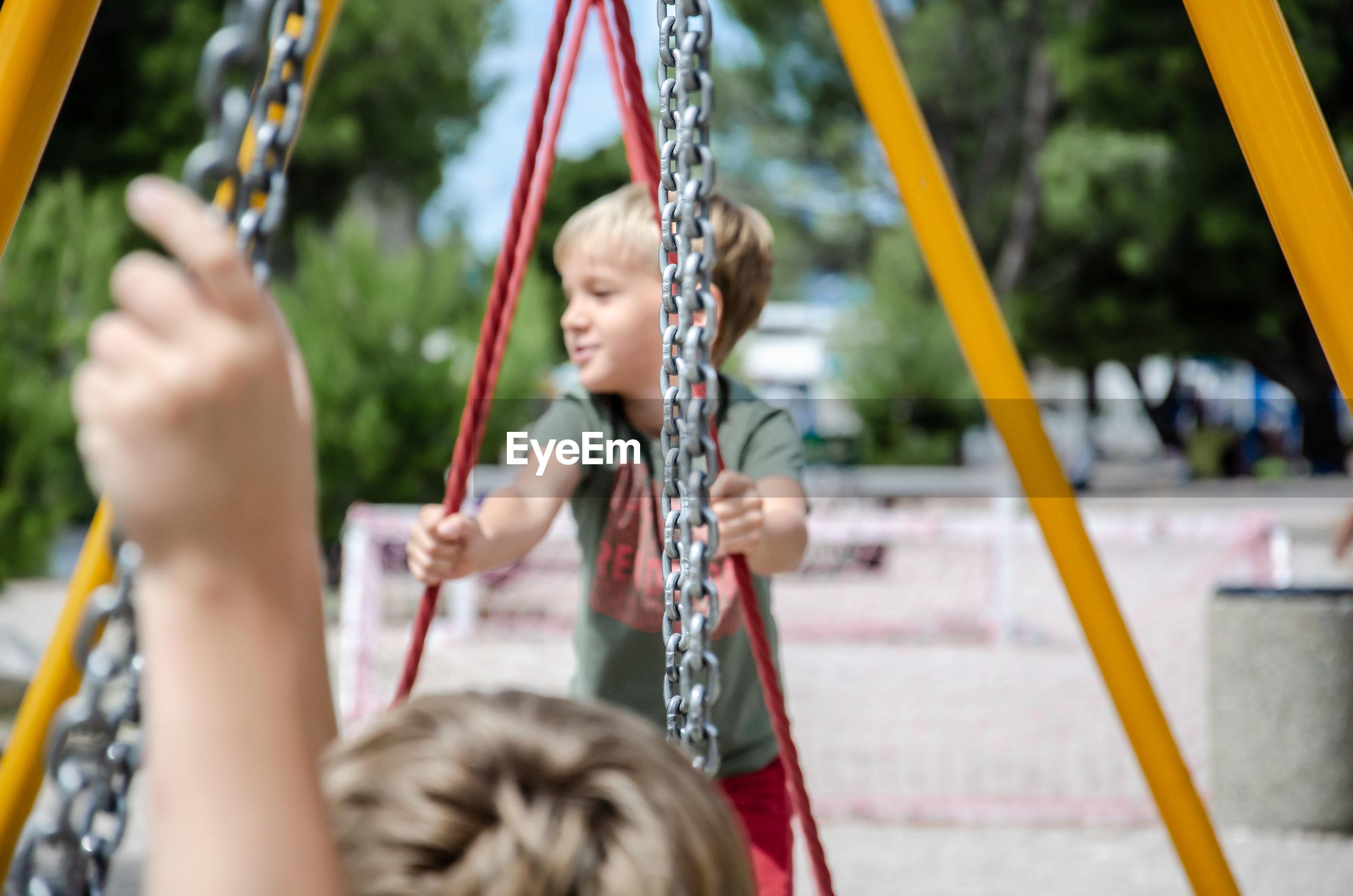 Children playing on swing at playground