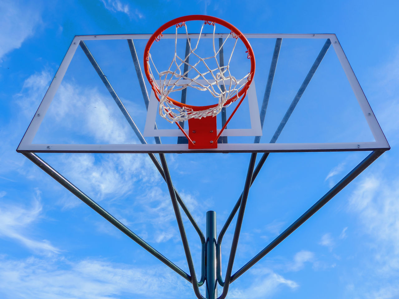 low angle view, sky, basketball hoop, basketball - sport, blue, cloud - sky, day, shape, net - sports equipment, nature, sport, geometric shape, no people, outdoors, circle, metal, design, red, sports equipment, directly below