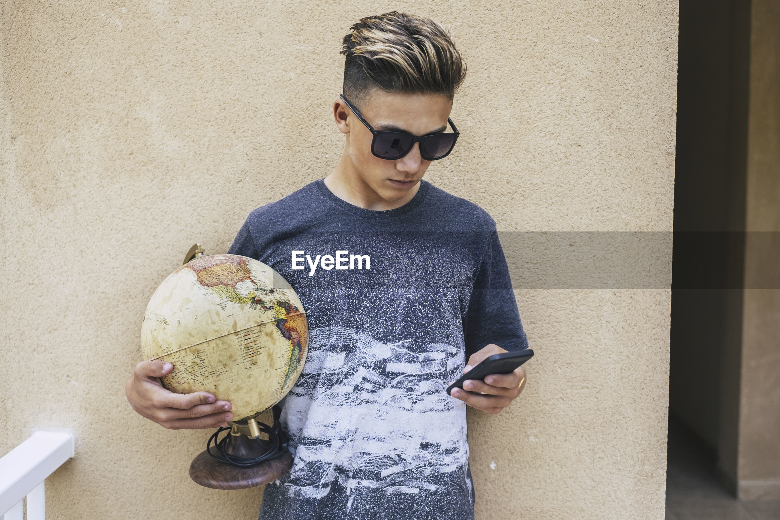 Teenage boy using mobile phone while holding globe against wall