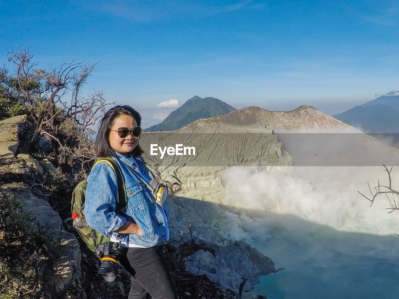 Woman Wearing Sunglasses Standing On Mountain Against Sky