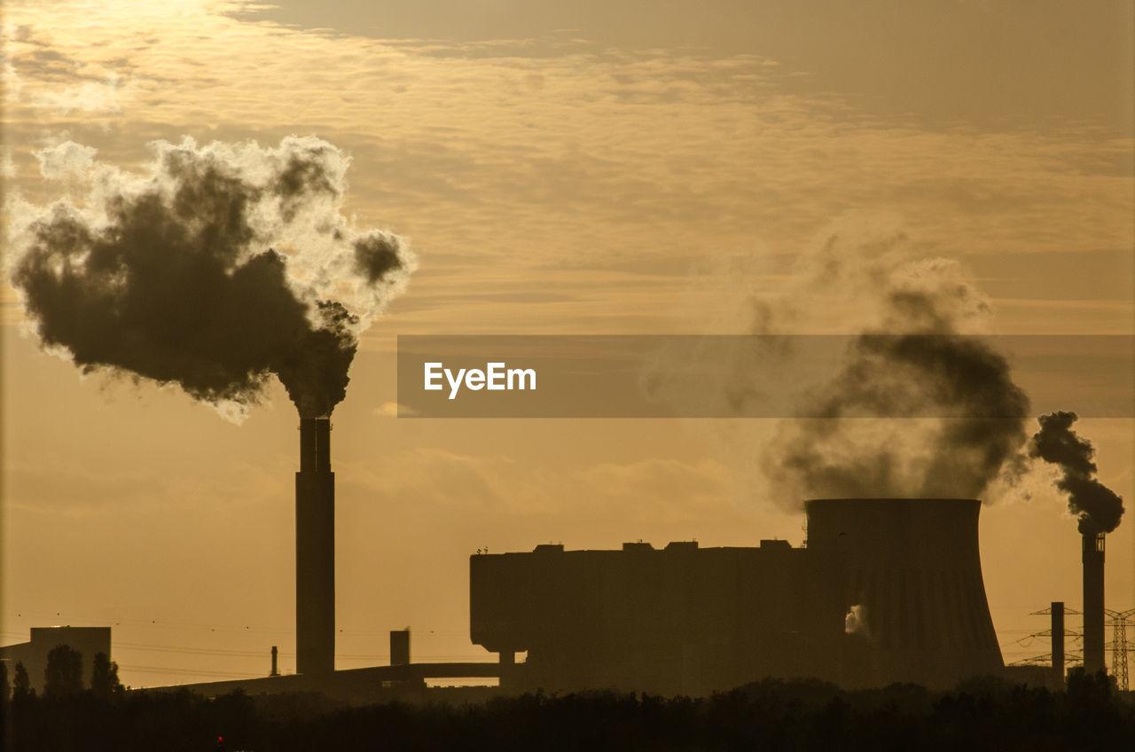 Smoke emitting from power plant against sunset sky