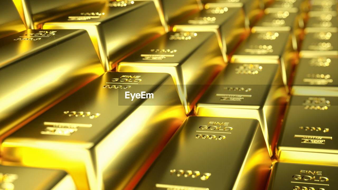 full frame, backgrounds, text, no people, close-up, gold colored, wealth, indoors, ingot, large group of objects, selective focus, western script, finance, shiny, gold, abundance, still life, metal, luxury, high angle view