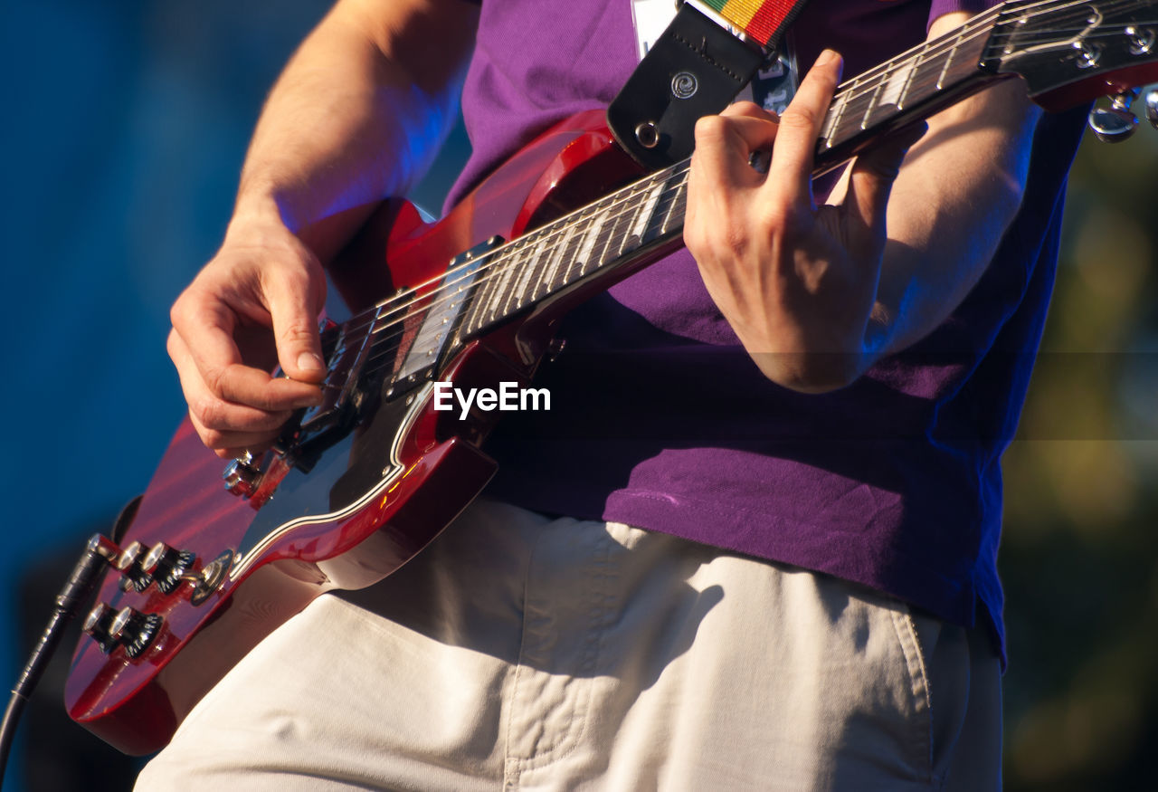 Midsection Of Man Playing Guitar At Concert