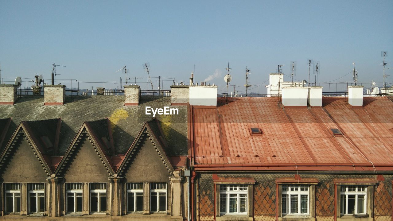 Antennas on roofs of residential buildings against clear sky
