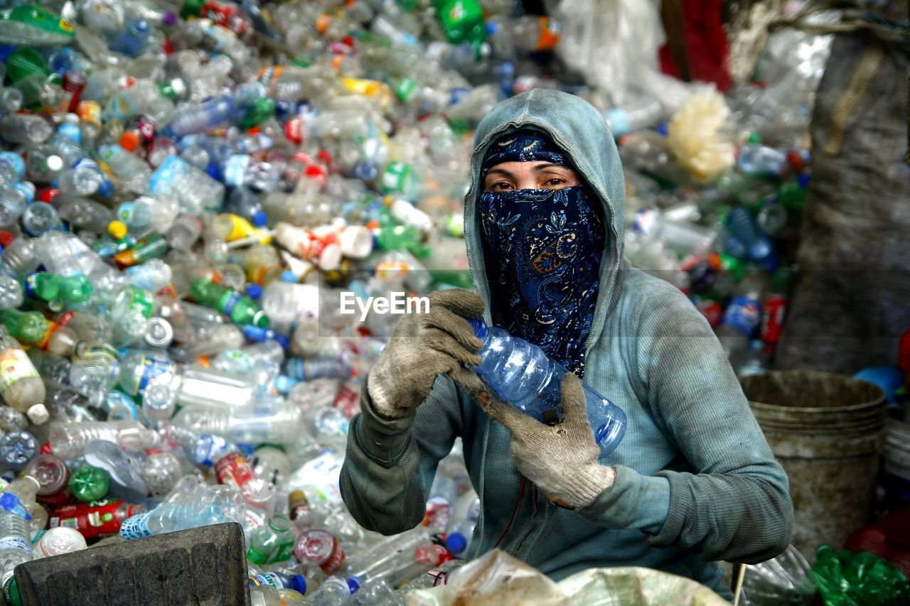 one person, portrait, real people, garbage, looking at camera, front view, plastic, environmental issues, holding, pollution, day, bottle, lifestyles, dirt, dirty, adult, outdoors, nature, young adult, plastic bag, obscured face