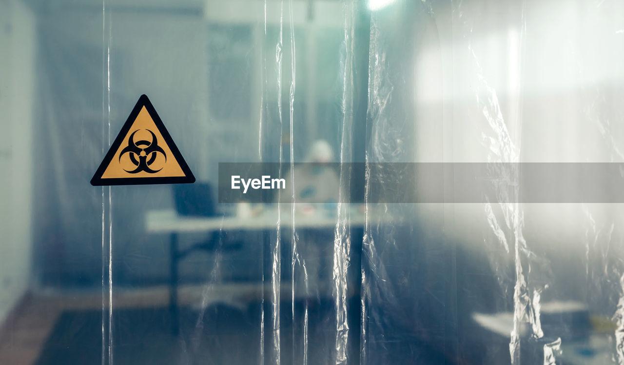 Scientist working in hospital seen through plastic curtain